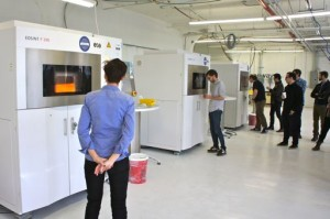 "Shapeways' Natalia Krasnodebska watches tour members gaze into red-hot laser-sintering printers at LIC 3DP ""Factory."""