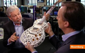 "Avi Reichental (left), President & CEO of 3D Systems Corporation, teaches 3DP'd guitar ""making"" at a trade show."