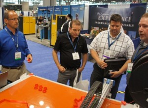 Joe Binka (far right), Development Engineer of 3DP Unlimited, expounds on his company's new large-format 3D printer, the 3DP1000, for booth guests at Automation Technology Expo (ATX) East, Javits Convention Center, 10 June 2014.