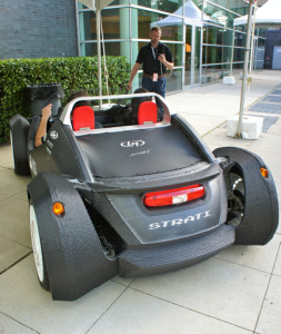 "Rear deck of the Local Motors ""Strati"" 3D-printed, open-source operational car parked outside MakerCon NY '14 at the NYSCI complex in Flushing Meadows, Queens; standing in the background is Jay Rogers, Local Motors' CEO & Co-Founder."
